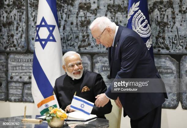 Israeli President Reuven Rivlin stands as Indian Prime Minister Narendra Modi signs the guest book during a welcome ceremony at the president's...