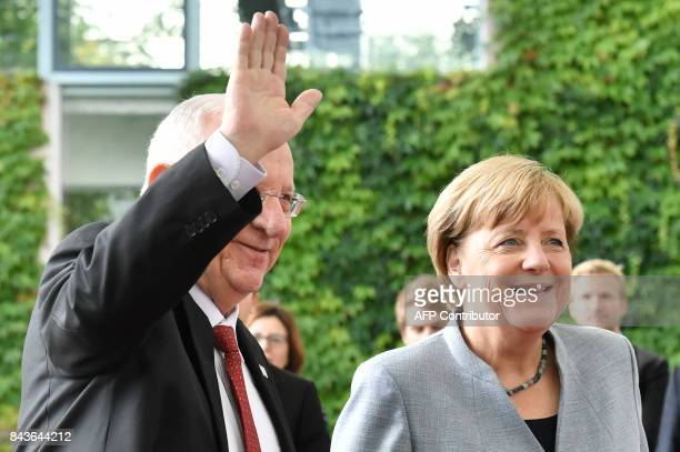 Israeli President Reuven Rivlin waves as German Chancellor Angela Merkel looks on at the chancellery in Berlin on September 7 2017 / AFP PHOTO / John...
