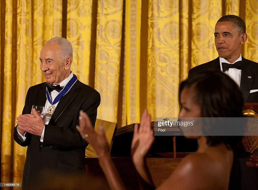 Israeli President <a gi-track='captionPersonalityLinkClicked' href=/galleries/search?phrase=Shimon+Peres&family=editorial&specificpeople=201775 ng-click='$event.stopPropagation()'>Shimon Peres</a> (L) and first lady <a gi-track='captionPersonalityLinkClicked' href=/galleries/search?phrase=Michelle+Obama&family=editorial&specificpeople=2528864 ng-click='$event.stopPropagation()'>Michelle Obama</a> (C) applaud as U.S. President <a gi-track='captionPersonalityLinkClicked' href=/galleries/search?phrase=Barack+Obama&family=editorial&specificpeople=203260 ng-click='$event.stopPropagation()'>Barack Obama</a> (R) recognizes former President Bill Clinton (not shown) following the presentation to Peres of the Presidential Medal of Freedom during a dinner in his honor in the East Room of the White House, on June 13, 2012 in Washington, D.C. Peres is the second Israeli, after Natan Sharansky, to receive the Presidential Medal of Freedom.