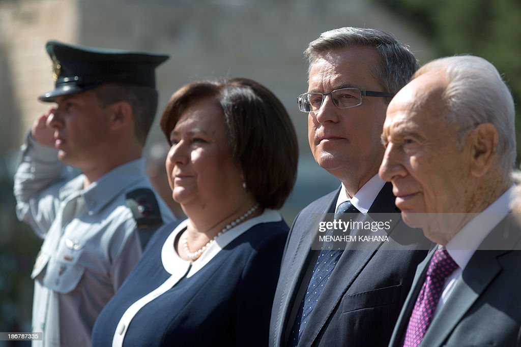 Israeli President Shimon Peres (R) and his Polish counterpart Bronislaw Komorowski (2nd-R) accompanied by his wife, Anna, listen to their national anthems during a welcoming ceremony at the presidential compound in Jerusalem on November 4, 2013.