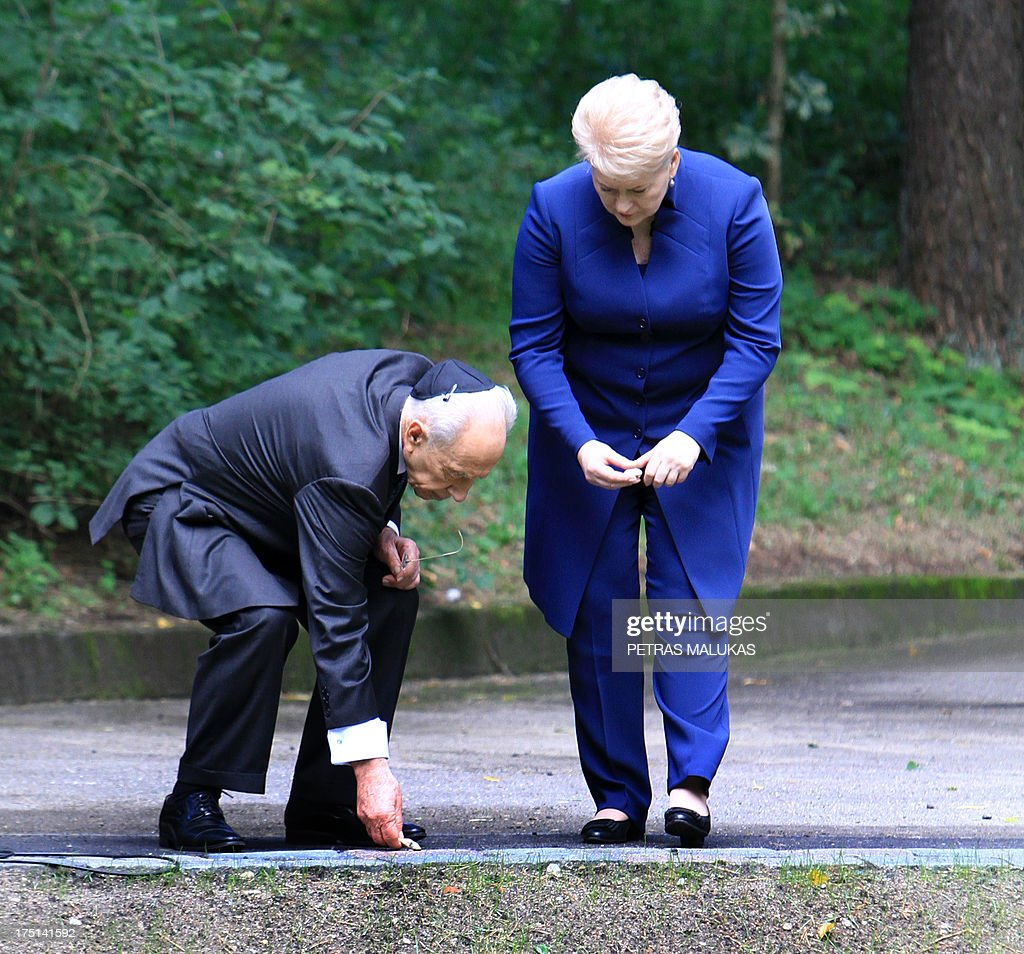 Israeli President Shimon Peres, (L) and Lithuania's counterpart Dalia Grybauskaite put stones on a part of the Paneriai memorial during the annual ceremony marking the Holocaust Remembrance day in Vilnius on August 1, 2013.