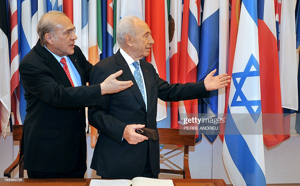 Israeli President Shimon Peres (R) and the Organisation for Economic Co-operation and Development (OECD) Secretary-General, Angel Gurria gesture prior to a meeting on March 8, 2013 at the OECD headquarters in Paris. AFP PHOTO / PIERRE ANDRIEU