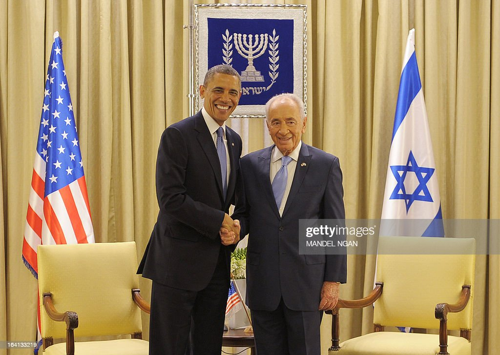 Israeli President Shimon Peres (R) and US President Barack Obama shake hands during a bilateral meeting at Peres' residence in Jerusalem on March 20, 2013. Obama arrived in Israel for the first time as US president, hoping to ease past tensions with his hosts and under pressure to narrow differences over handling Iran's nuclear threat. AFP PHOTO/MANDEL NGAN