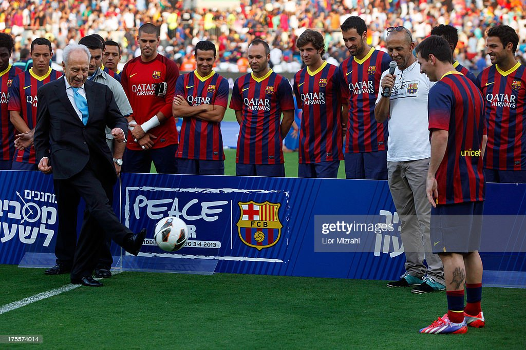Israeli President <a gi-track='captionPersonalityLinkClicked' href=/galleries/search?phrase=Shimon+Peres&family=editorial&specificpeople=201775 ng-click='$event.stopPropagation()'>Shimon Peres</a> passes a ball to FC Barcelona player <a gi-track='captionPersonalityLinkClicked' href=/galleries/search?phrase=Lionel+Messi&family=editorial&specificpeople=453305 ng-click='$event.stopPropagation()'>Lionel Messi</a> (R) during a training session on August 4, 2013 in Tel Aviv, Israel. Members of the FC Barcelona squad have travelled to the Middle East to visit Israel and the West Bank as part of a two-day 'peace tour'.