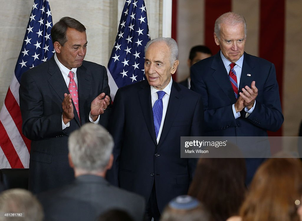 Israeli President Shimon Peres (C) receives applause from U.S. Vice President Joseph Biden (R) and House Speaker John Boehner (R-OH) after being presented with the Congressional Gold Medal during a ceremony at the U.S. Capitol, June 26, 2014 in Washington, DC. The Congressional Gold Medal recognizes those who have performed an achievement that has an impact on American history and culture. Photo by Mark Wilson/Getty Images)
