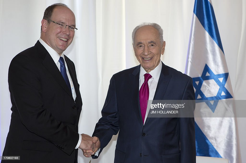 Israeli President Shimon Peres (R) shakes hands with Prince Albert II of Monaco in at a convention centre in Jerusalem on June 18, 2013, a few hours before the gala celebrating the Israeli leader's 90th birthday. A slew of stars, politicians and public figures were flocking to Jerusalem to take part in Peres's birthday celebrations.