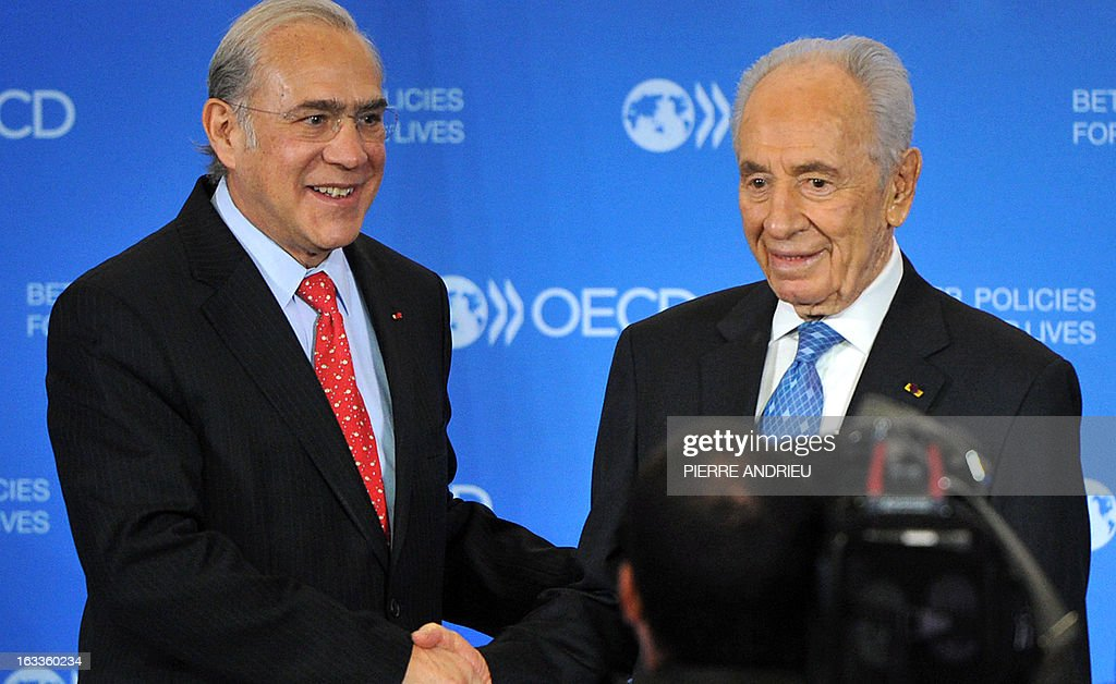 Israeli President Shimon Peres (R) shakes hands with the Organisation for Economic Co-operation and Development (OECD) Secretary-General, Angel Gurria prior to a meeting on March 8, 2013 at the OECD headquarters in Paris.