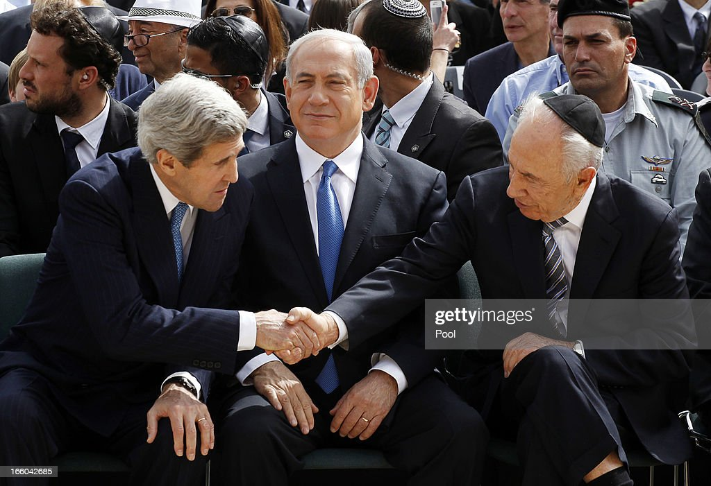 Israeli President Shimon Peres (R) shakes hands with US Secretary of State John Kerry (L) as Prime Minister Benjamin Netanyahu sits in between them during the annual ceremony for Holocaust Remembrance Day at the Yad Vashem memorial on April 8, 2013 in Jerusalem, Israel. Across the world, people commemorated the six million Jews murdered by the Nazi regime during World War II between 1933 and 1945. U.S. Secretary of State John Kerry's visit is in an attempt to restart mideast peace talks between Israeli and Palestinians officials.