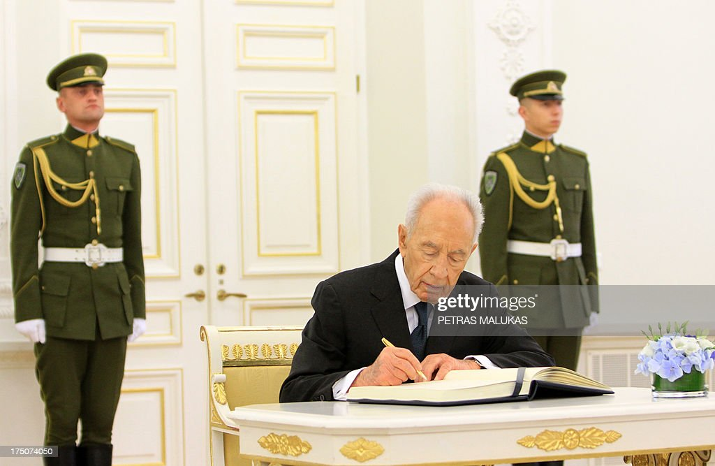 Israeli President Shimon Peres (C) signs the guest book on July 31, 2013 at the presidential palace in Vilnius, Lithuania. AFP PHOTO / PETRAS MALUKAS