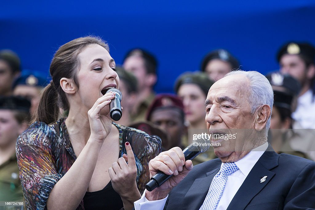 Israeli President <a gi-track='captionPersonalityLinkClicked' href=/galleries/search?phrase=Shimon+Peres&family=editorial&specificpeople=201775 ng-click='$event.stopPropagation()'>Shimon Peres</a> (R) sings during a 'Singing Independence' ceremony in honour of outstanding soldiers, as part of Israel's 65th Independence Day celebrations, at the President's Residence on April 16, 2013 in Jerusalem, Israel. 120 outstanding soldiers and officers were honoured during the event.