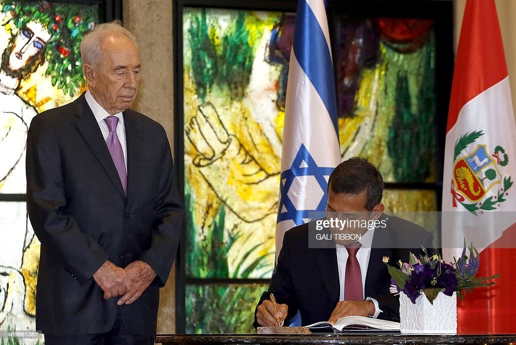 Israeli President Shimon Peres (L) stands next to his Peruvian counterpart Ollanta Humala as he signs the guestbook during a welcoming ceremony at the presidential compound in Jerusalem, on February 17, 2014. Humala met his Israeli counterpart Peres before a working lunch with Prime Minister Benjamin Netanyahu. AFP PHOTO/GALI TIBBON