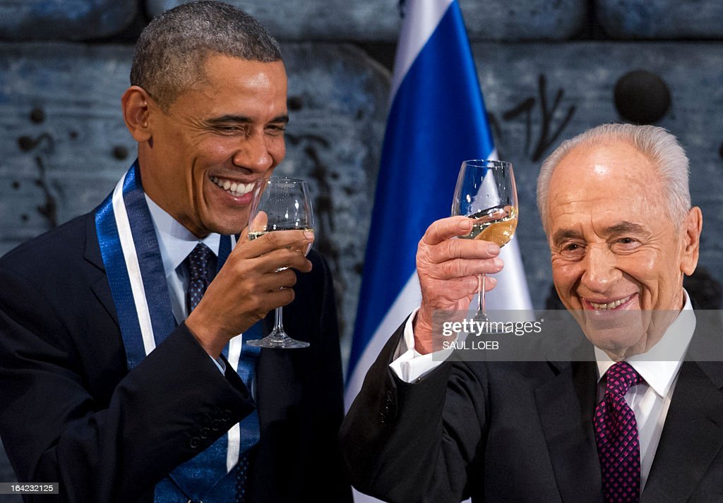 Israeli President Shimon Peres (R) toasts US President Barack Obama after presenting him with the Presidential Medal of Distinction, the highest civilian honor in Israel, during an official State Dinner at the President's residence in Jerusalem, March 21, 2013, on the second day of Obama's 3-day trip to Israel and the Palestinian territories. AFP PHOTO / Saul LOEB