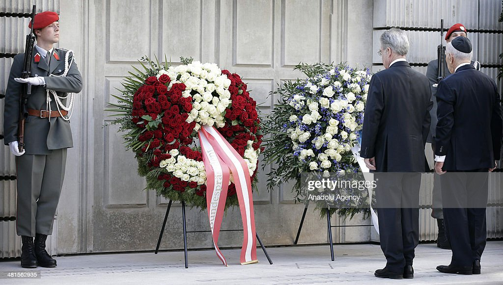 Israeli President Shimon Peres (R) visits the memorial for Austrian victims of the Holocaust with President of Austria Heinz Fischer (L) in Vienna, Austria, on March 30, 2014.