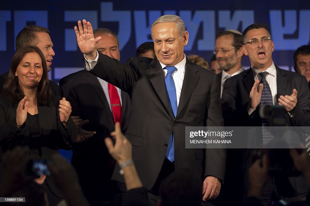 Israeli Prime Minister and chairman of the Likud party Benjamin Netanyahu (C) waves to supporters in the Tel Aviv party headquarters early on January 23, 2013 after his Likud-Beitenu list won the Israeli general election. Netanyahu said it was necessary to form the 'broadest possible government' after his Likud-Beitenu list won a narrow election victory, with the centrist Yesh Atid in second place. AFP PHOTO/MENAHEM KAHANA