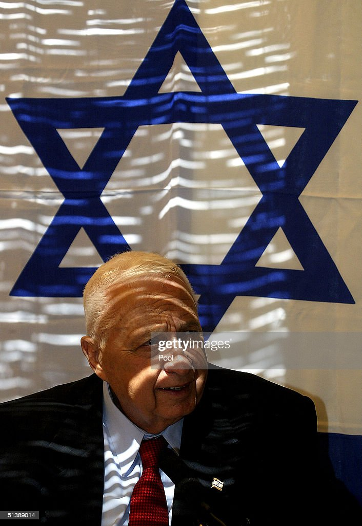 Israeli Prime Minister Ariel Sharon, backed by an Israeli flag, looks on during a meeting with immigrant Israeli soldiers from around Israel invited to his traditional Sukkot hut for a visit, on the fifth day of Sukkot holiday, at the Prime Minister's residence on October 4, 2004 in Jerusalem, Israel. The holiday of Sukkot, also known as the Feast of Tabernacles, is named for the shelters the Biblical Israelites lived in as they wandered the desert for 40 years.