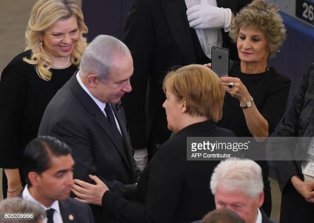 Israeli Prime Minister Benjamin Netanyahou and German Chancellor Angela Merkel shake hands at the European Parliament in Strasbourg eastern France on...