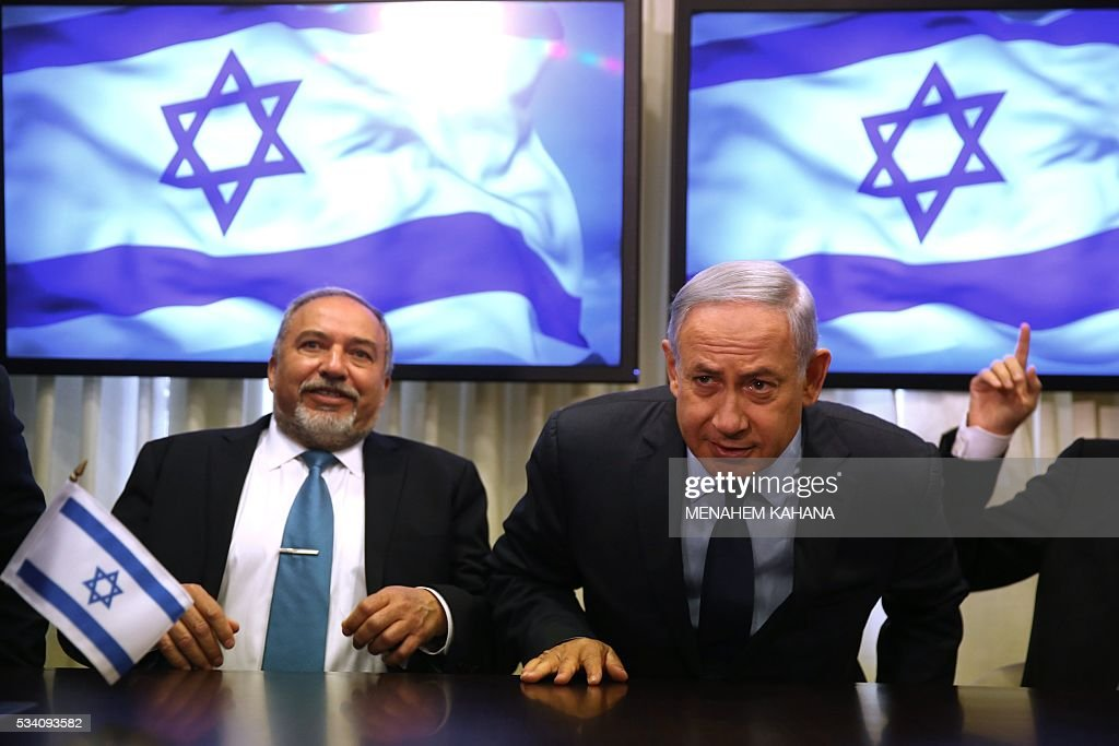 Israeli Prime Minister Benjamin Netanyahu (R) and Avigdor Lieberman (L), the head of hardline nationalist party Yisrael Beitenu, are seen during a ceremony in which they signed a coalition agreement on May 25 2016 at the Knesset, the Israeli parliament in Jerusalem. A deal has been reached to bring far-right former foreign minister Avigdor Lieberman and his Yisrael Beitenu party into Israel's governing coalition pushing it further to the right. Prime Minister Benjamin Netanyahu will expand his coalition to 66 lawmakers and make Lieberman defence minister. / AFP / MENAHEM