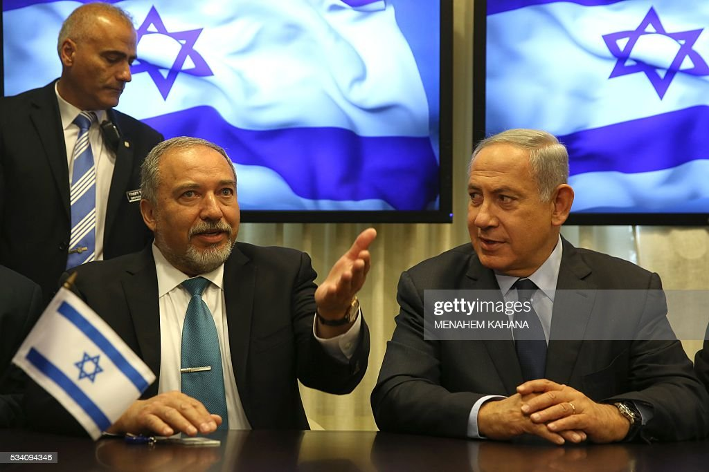Israeli Prime Minister Benjamin Netanyahu (R) and Avigdor Lieberman (L), the head of hardline nationalist party Yisrael Beitenu, are seen during a ceremony in which they signed a coalition agreement on May 25, 2016 at the Knesset, the Israeli parliament in Jerusalem. A deal has been reached to bring far-right former foreign minister Avigdor Lieberman and his Yisrael Beitenu party into Israel's governing coalition pushing it further to the right. Prime Minister Benjamin Netanyahu will expand his coalition to 66 lawmakers and make Lieberman defence minister. / AFP / MENAHEM