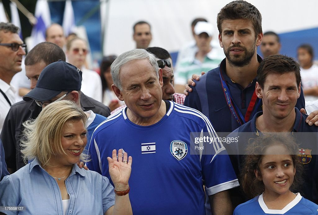 Israeli Prime Minister Benjamin Netanyahu (C) and his wife Sara (L) pose for a picture with FC Barcelona players Gerard Pique (top) and Lionel Messi (R), during a football event with young Israeli cancer patients on August 4, 2013 near Tel Aviv, Israel. Members of the FC Barcelona squad have travelled to the Middle East to visit Israel and the West Bank as part of a two-day 'peace tour'.