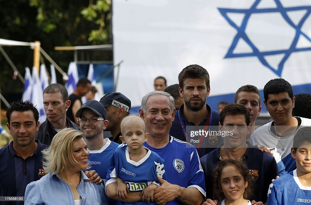 Israeli Prime Minister Benjamin Netanyahu (C) and his wife Sara (2nd-L) pose for a picture with FC Barcelona players Xavi (L), Gerard Pique (top) and Lionel Messi (R), during a football event with young Israeli cancer patients, on August 4, 2013 near Tel Aviv, Israel. Members of the FC Barcelona squad have travelled to the Middle East to visit Israel and the West Bank as part of a two-day 'peace tour'.