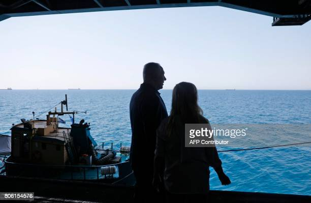 Israeli Prime Minister Benjamin Netanyahu and his wife Sara pose for a photo during a tour aboard the US aircraft carrier USGeorge H W Bush as it...