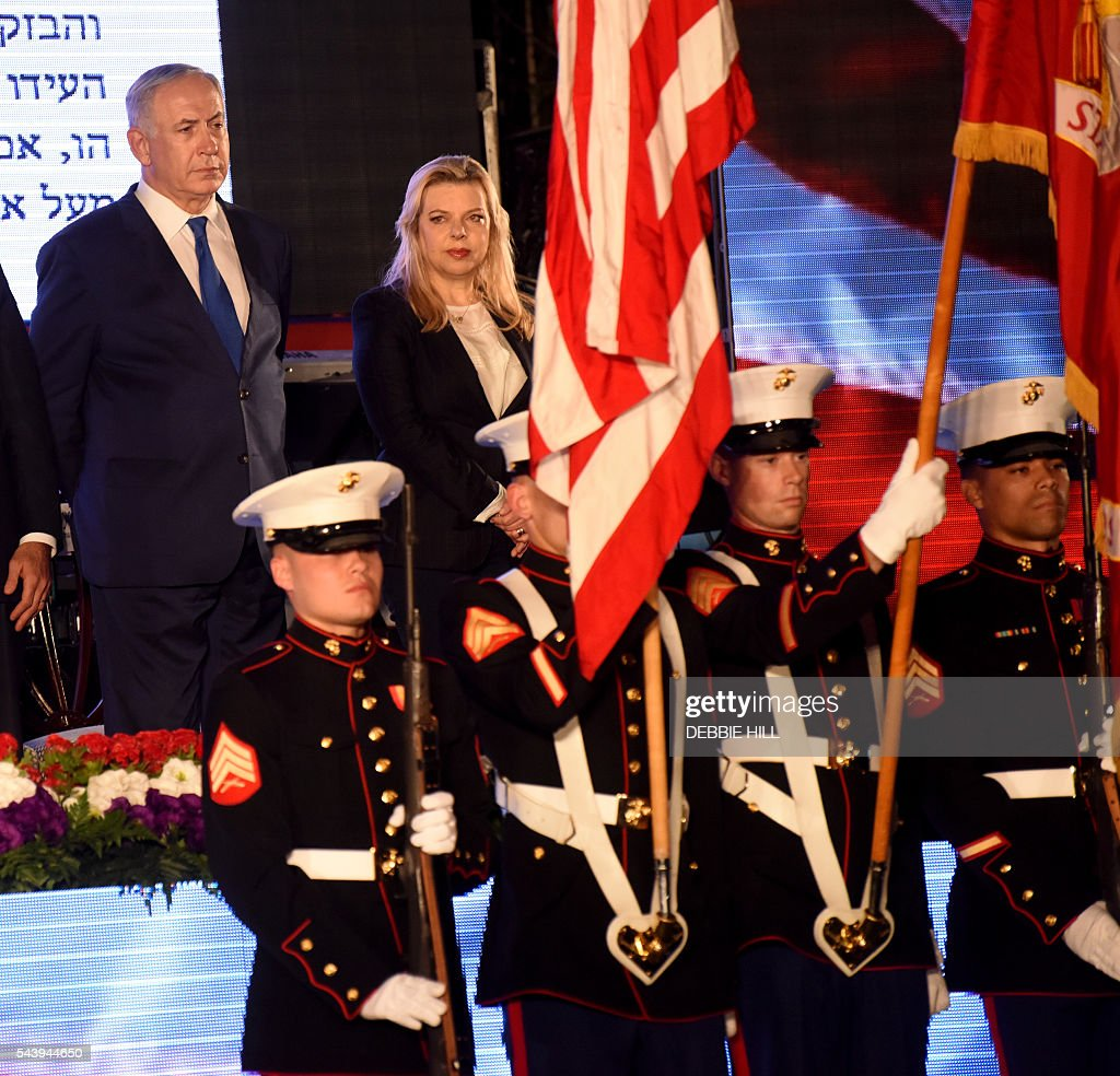 Israeli Prime Minister Benjamin Netanyahu (top-L) and his wife Sarah stand during a ceremony marking the US Independence Day at the residence of the US Ambassador to Israel in Herzliya, near Tel Aviv, on June 30, 2016. / AFP / POOL / DEBBIE