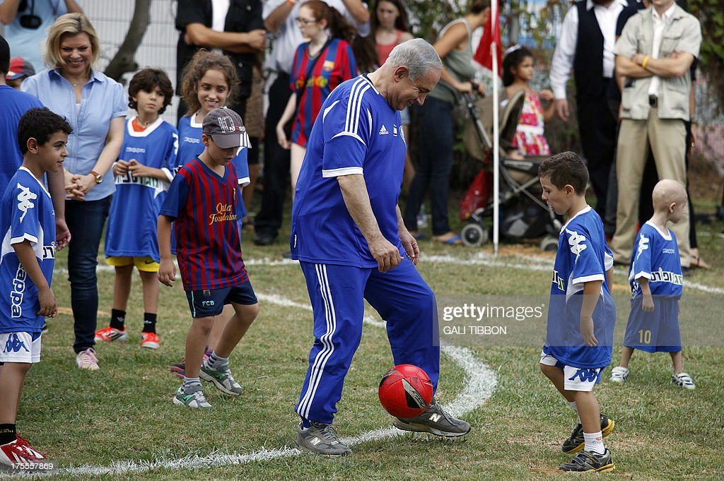 Israeli Prime Minister Benjamin Netanyahu (C) and his wife Sara (L) take part in a football event with young Israeli cancer patients, attended by FC Barcelona players, near Tel Aviv on August 4, 2013.
