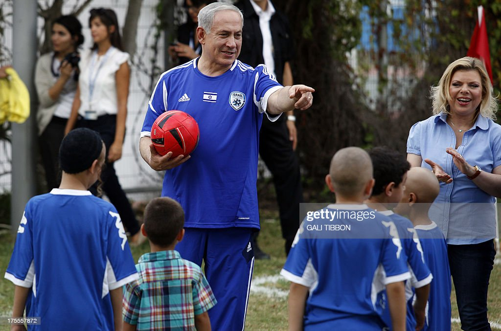 Israeli Prime Minister Benjamin Netanyahu (C) and his wife Sara (R) take part in a football event with young Israeli cancer patients, attended by FC Barcelona players, near Tel Aviv on August 4, 2013.