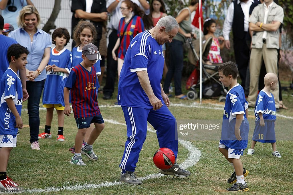 Israeli Prime Minister Benjamin Netanyahu (C) and his wife Sara (L) take part in a football event with young Israeli cancer patients, attended by FC Barcelona players, on August 4, 2013 near Tel Aviv, Israel. Members of the FC Barcelona squad have travelled to the Middle East to visit Israel and the West Bank as part of a two-day 'peace tour'.