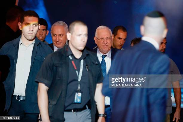 Israeli Prime Minister Benjamin Netanyahu and President Reuven Rivlin walk surrounded by their personal security detail during a ceremony marking the...