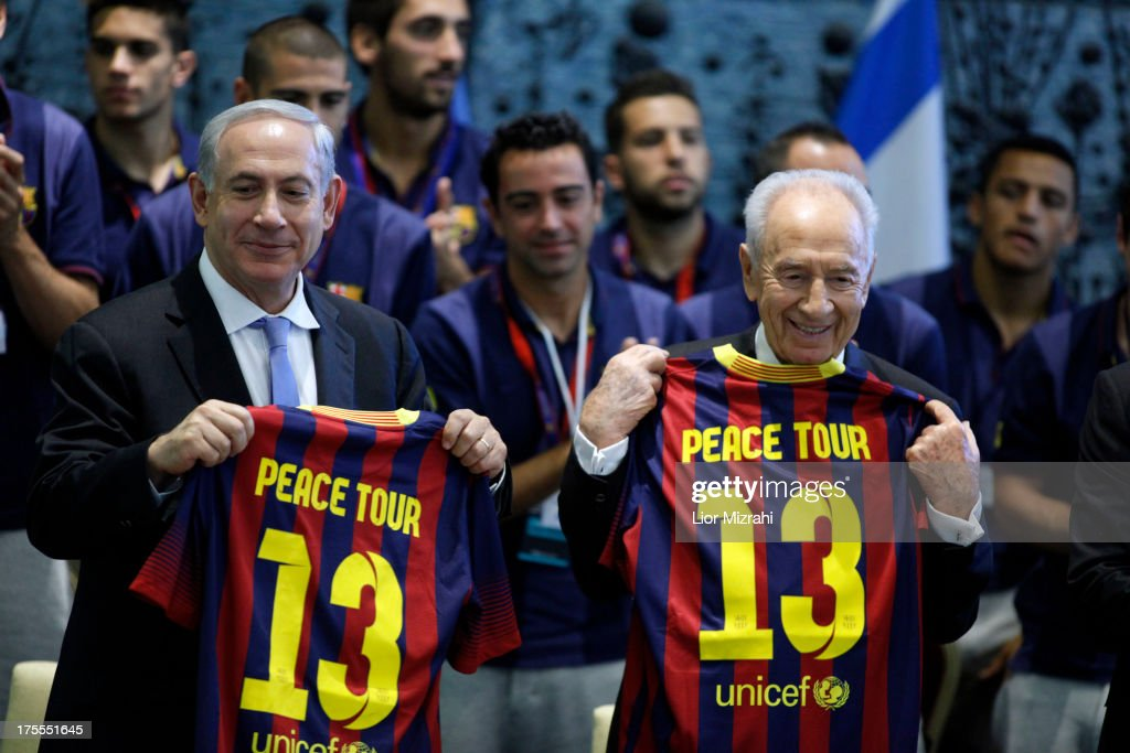 Israeli Prime Minister Benjamin Netanyahu (L) and President Shimon Peres hold team jerseys during a ceremony with Members of FC Barcelona at the President house on August 4, 2013 in Jerusalem, Israel. Members of the FC Barcelona squad have travelled to the Middle East to visit Israel and the West Bank as part of a two-day 'peace tour'.