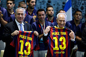Israeli Prime Minister Benjamin Netanyahu and President Shimon Peres hold team jerseys during a ceremony with Members of FC Barcelona at the...