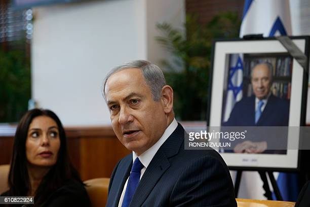 Israeli Prime Minister Benjamin Netanyahu and Sports and Culture Minister Miri Regev are seen next to a photograph of former Israeli president Shimon...