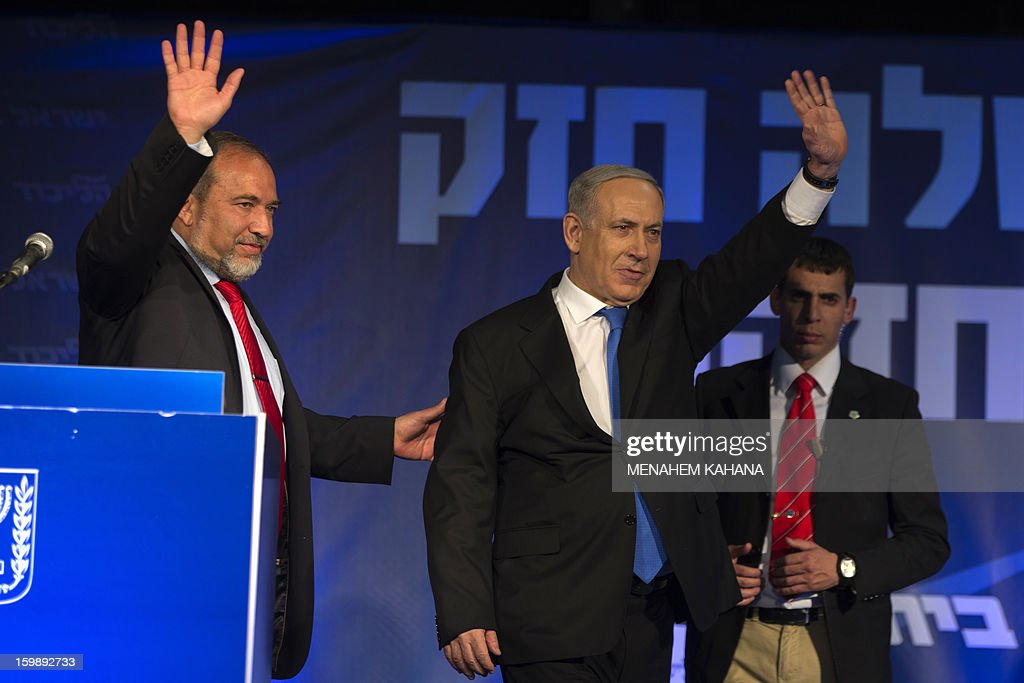 Israeli Prime Minister Benjamin Netanyahu (C) and ultra-nationalist Avigdor Lieberman (L) of the Likud-Beitenu coalition wave to supporters at the party headquarters in Tel Aviv early on January 23, 2013 after their Likud-Beitenu list won the Israeli general elections. Netanyahu said it was necessary to form the 'broadest possible government' after his Likud-Beitenu list won a narrow election victory, with the centrist Yesh Atid in second place.