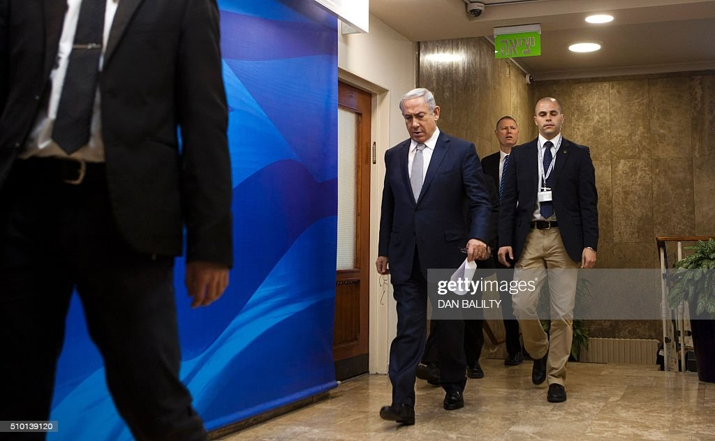 Israeli Prime Minister Benjamin Netanyahu (C) arrives for the weekly cabinet meeting at the PM's office in Jerusalem on February 14, 2016. / AFP / POOL / DAN BALILTY