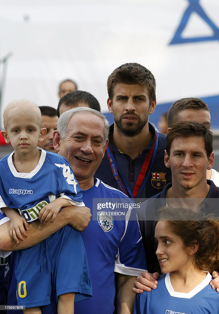 Israeli Prime Minister Benjamin Netanyahu (L) carries a young Israeli cancer patient while posing for a picture with FC Barcelona players Gerard Pique (top) and Lionel Messi (R), during a football event with young Israeli cancer patients, near Tel Aviv on August 4, 2013.