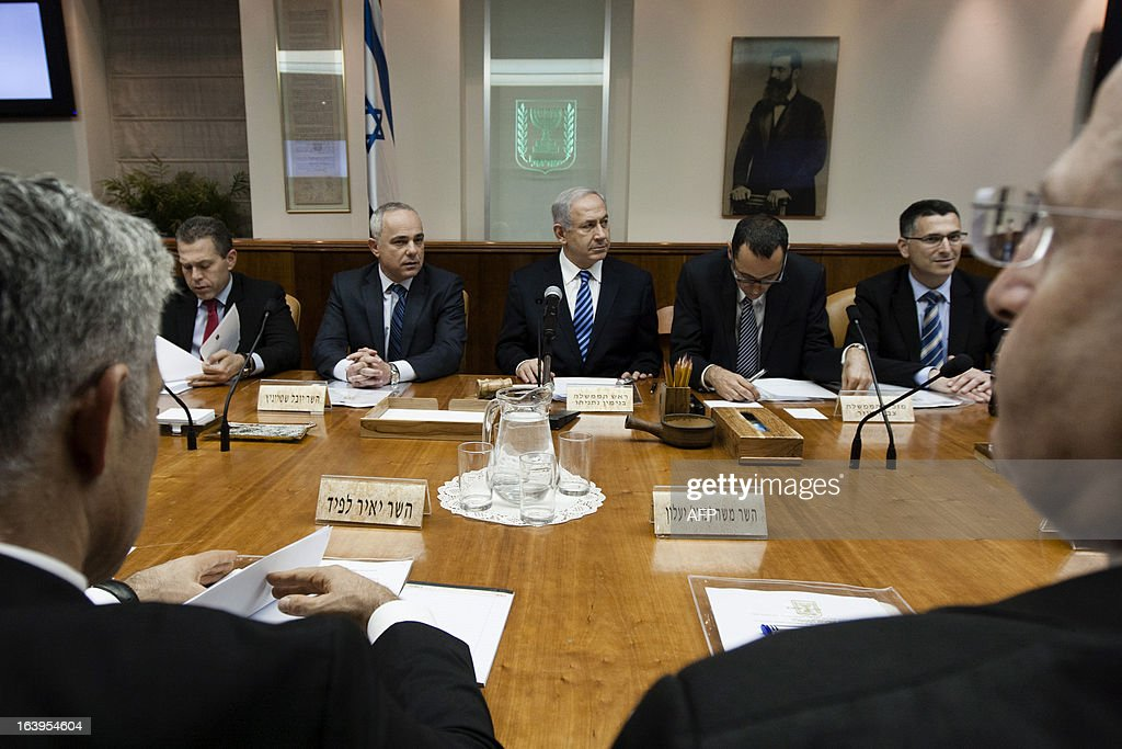 Israeli Prime Minister Benjamin Netanyahu (C) chairs the first cabinet meeting after the swearing-in of the new Israeli government in Jerusalem on March 18, 2013. A new Israeli governing coalition with a strong showing of pro-settlement hardliners formally took office after confirmation by parliament days before a landmark US presidential visit.
