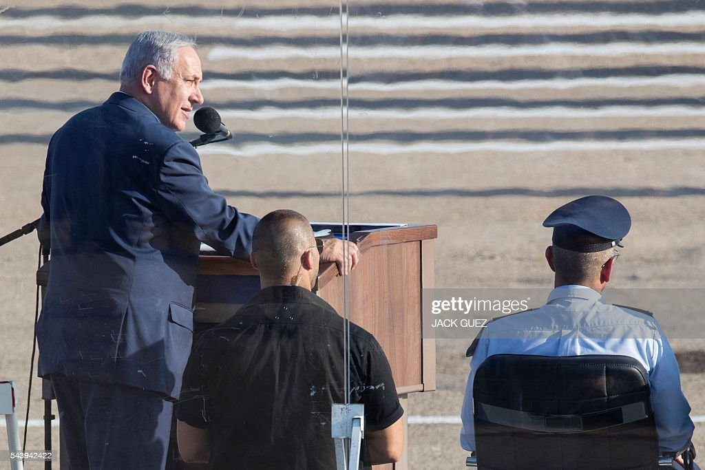 Israeli Prime Minister Benjamin Netanyahu (L) delivers a speech during a graduation ceremony of Israeli air force pilots at the Hatzerim base in the Negev desert, near the southern city of Beer Sheva, on June 30, 2016. / AFP / JACK