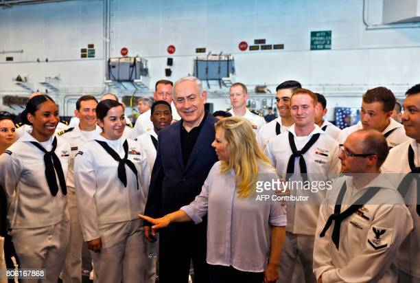 Israeli Prime Minister Benjamin Netanyahu his wife Sara speak with American soldiers during a visit on the US aircraft carrier USS George H W Bush as...