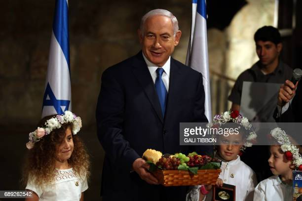 Israeli Prime Minister Benjamin Netanyahu holds a basket of fruit he received from local children in memory of the Biblical commandment for farmers...