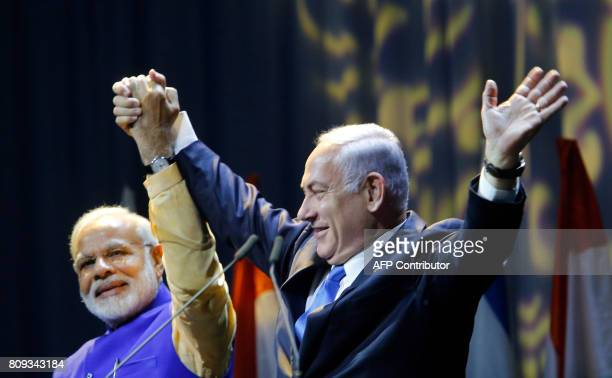 Israeli Prime Minister Benjamin Netanyahu holds hands with his Indian counterpart Narendra Modi during a meeting with Indian community at the Tel...
