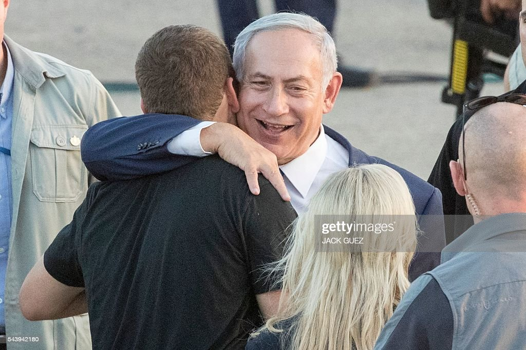 Israeli Prime Minister Benjamin Netanyahu hugs his son Avner during a graduation ceremony of Israeli air force pilots at the Hatzerim base in the Negev desert, near the southern city of Beer Sheva, on June 30, 2016. / AFP / JACK