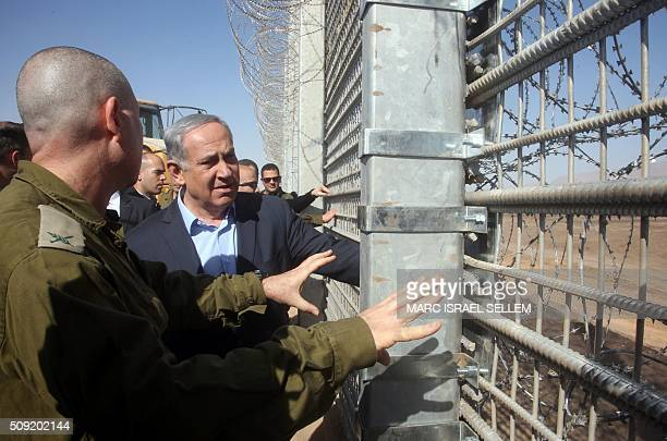 Israeli Prime Minister Benjamin Netanyahu listens to an army officer during a visit to the construction site of a new military border fence between...