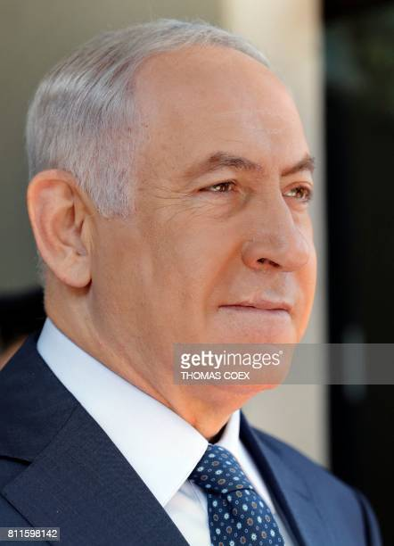 Israeli Prime Minister Benjamin Netanyahu looks on as he waits with Israeli President Reuven Rivlin for the arrival of Rwanda's president during a...
