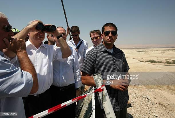 Israeli Prime Minister Benjamin Netanyahu looks through binoculars on a ridge overlooking the Allenby Crossing terminal and the border with Jordan as...