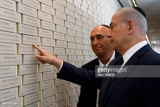 Israeli Prime Minister Benjamin Netanyahu points at his brother's name Yoni Netanyahu who was killed during Operation Entebbe in Uganda as he visits...