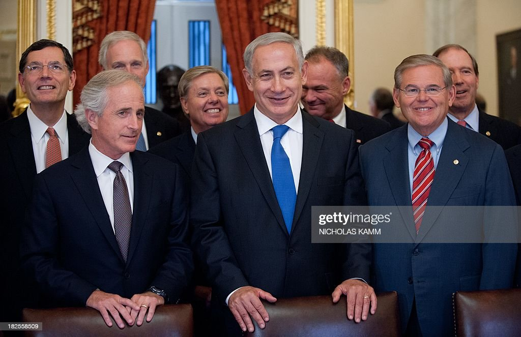 Israeli Prime Minister Benjamin Netanyahu (C) poses with US Senate Foreign Relations Committee chairman Robert Menendez (R) and other committee members at the Capitol on September 30, 2013. AFP PHOTO/Nicholas KAMM