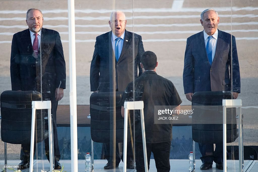 Israeli Prime Minister Benjamin Netanyahu, President Reuven Rivlin and Defence Minister Avigdor Lieberman stand for the playing of their national anthem during a graduation ceremony of Israeli air force pilots Hatzerim base in the Negev desert, near the southern Israeli city of Beer Sheva, on June 30, 2016. / AFP / JACK