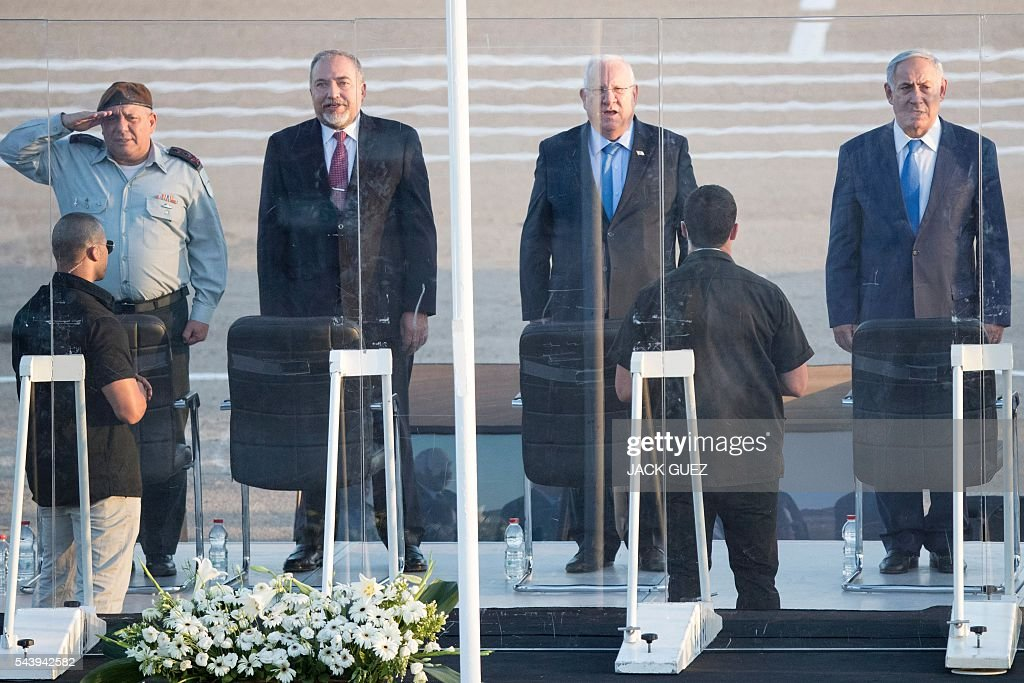 Israeli Prime Minister Benjamin Netanyahu, President Reuven Rivlin, Defence Minister Avigdor Lieberman and Chief of staff Gadi Eizenkot stand for the playing of their national anthem during a graduation ceremony of Israeli air force pilots Hatzerim base in the Negev desert, near the southern Israeli city of Beer Sheva, on June 30, 2016. / AFP / JACK