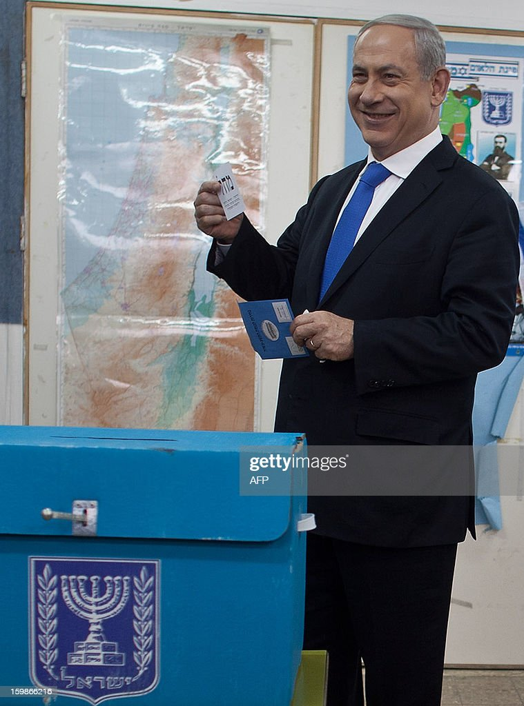 Israeli Prime Minister Benjamin Netanyahu readies to cast his ballot at a polling station in Jerusalem, on January 22, 2013, as Israel residents started to vote in the 19th Israeli general election. Polls opened on January 22 in Israel's general election, which is expected to return Netanyahu to power at the head of a government of hardline right-wing and religious parties. AFP PHOTO/URIEL SINAI-POOL